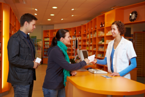pharmacist assisting customers in the counter
